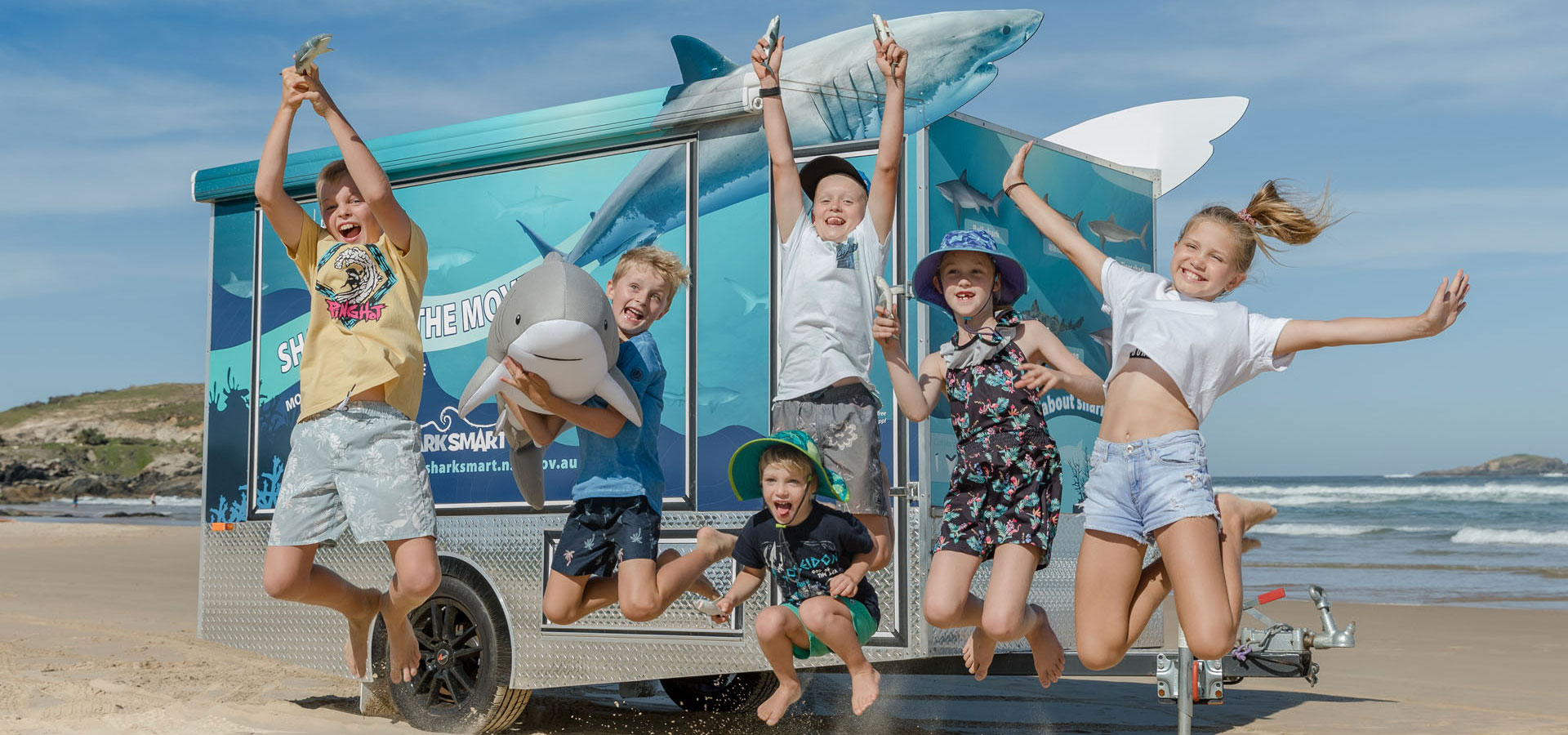 Kids are jumping with joy in front of the shark trailer